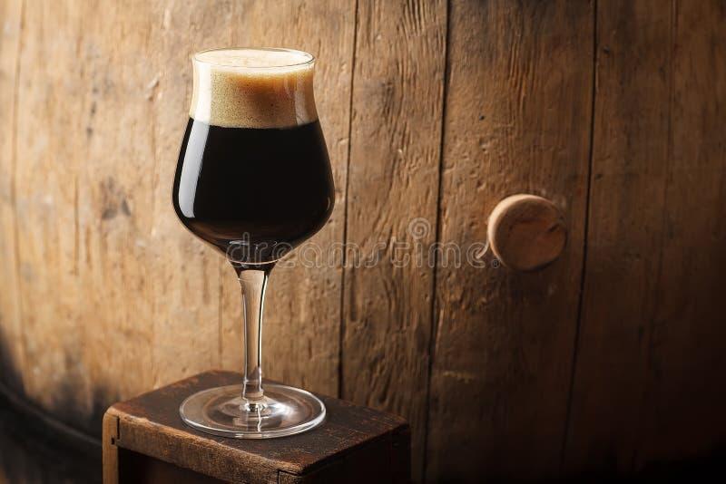 在桶附近的烈性黑啤酒 库存图片