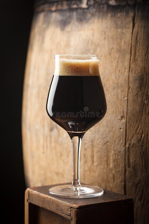 在桶附近的烈性黑啤酒 免版税库存照片