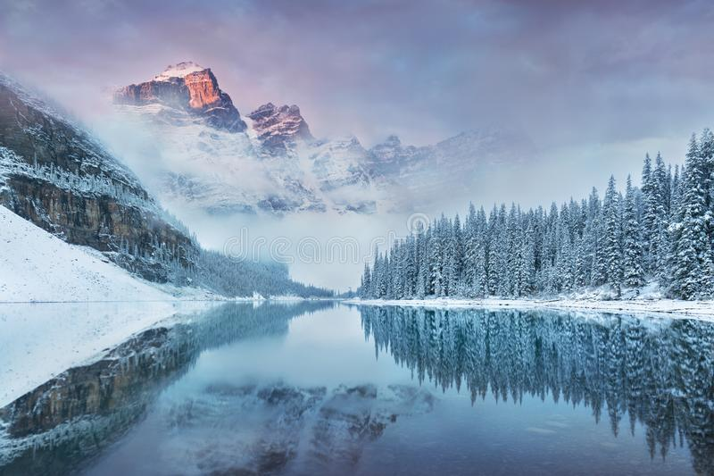 在梦莲湖的第一个雪早晨在班夫国家公园阿尔伯塔加拿大 冬天大气的积雪的冬天山湖 免版税库存照片