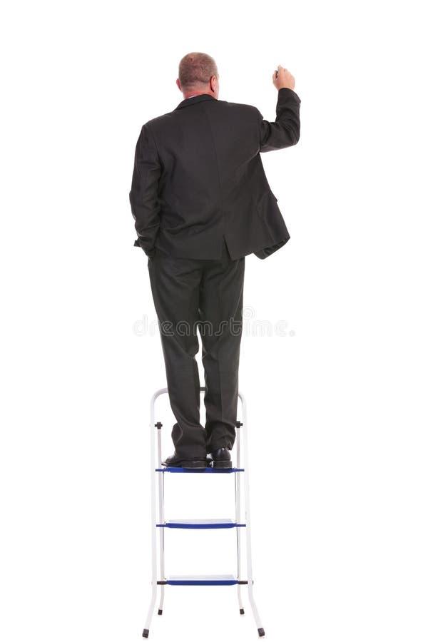 在梯子的商人文字 库存照片