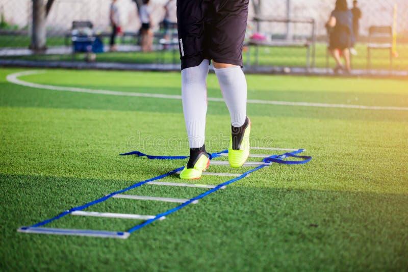 在梯子钻子之间的年轻男孩足球运动员跑步和跃迁橄榄球训练的 梯子橄榄球的钻子锻炼或 免版税库存照片