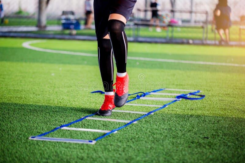 在梯子钻子之间的年轻男孩足球运动员跑步和跃迁橄榄球训练的 梯子橄榄球的钻子锻炼或 免版税库存图片