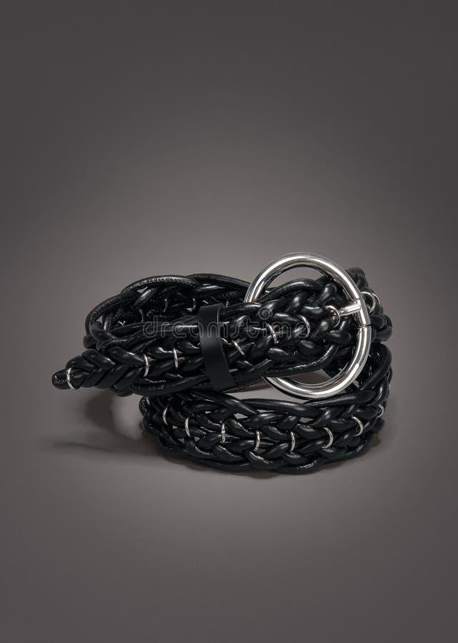 在梯度灰色背景的被编织的黑皮带 库存图片
