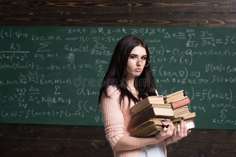 在检查前的严肃的女性年轻学生 运载两堆重的书的玻璃的深色的女孩 库存图片