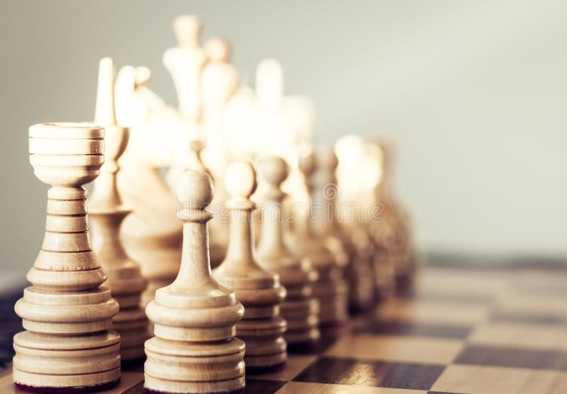 在棋枰的木棋子,在白色背景的领导概念 库存照片