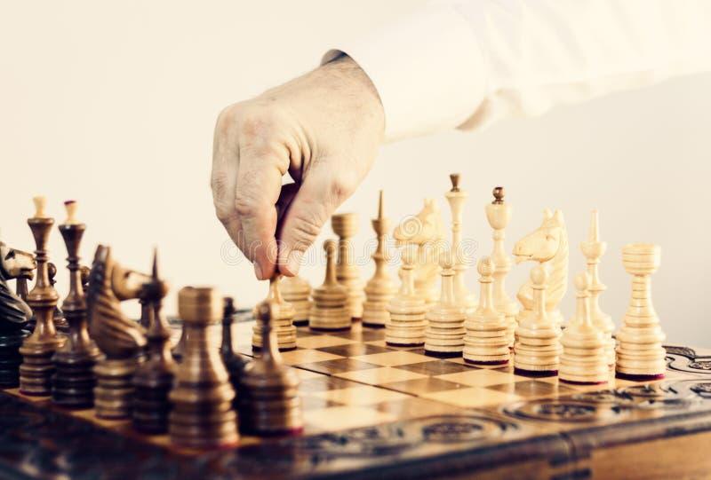在棋枰,下棋比赛球员的木棋子采取行动 免版税库存图片