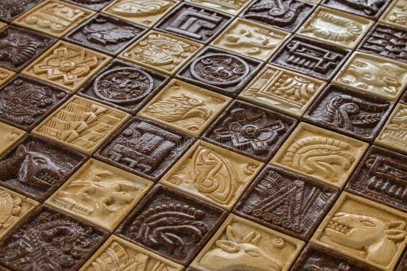 在棋盘的古老玛雅动物雕刻棋的作战概念和马和鱼和太阳神和当地美洲印第安人l 图库摄影