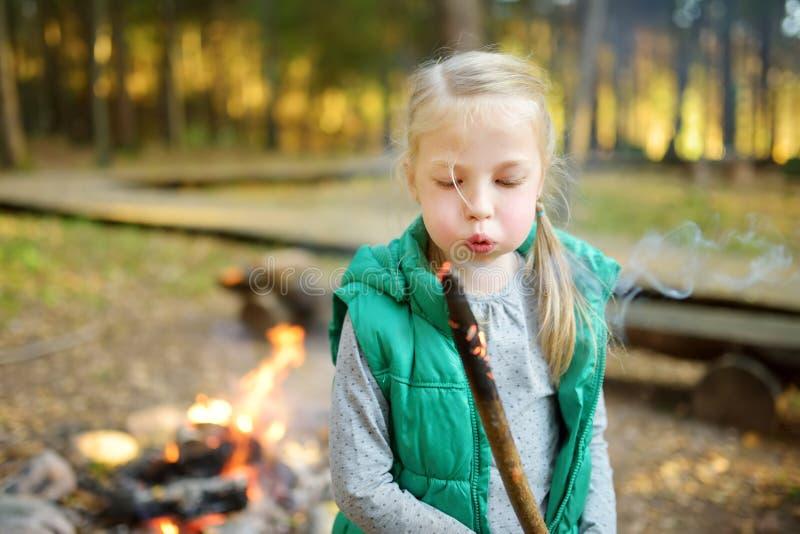 在棍子的可爱的少女烤蛋白软糖在篝火 孩子获得乐趣在阵营火 野营与孩子在秋天森林里 免版税图库摄影