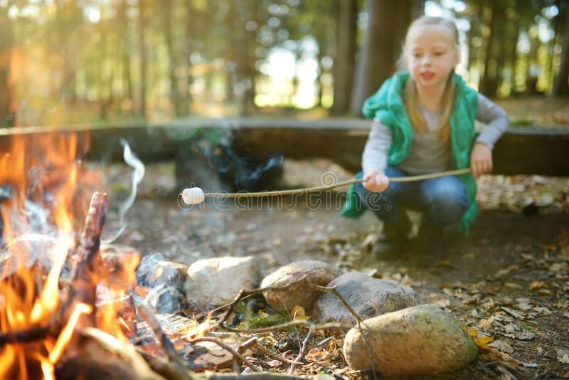 在棍子的可爱的少女烤蛋白软糖在篝火 孩子获得乐趣在阵营火 野营与孩子在秋天森林里 库存图片