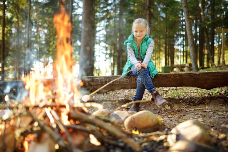 在棍子的可爱的少女烤蛋白软糖在篝火 孩子获得乐趣在阵营火 野营与孩子在秋天森林里 免版税库存图片