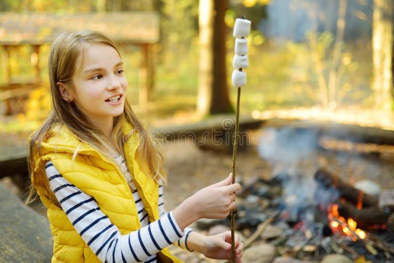 在棍子的可爱的少女烤蛋白软糖在篝火 孩子获得乐趣在阵营火 野营与孩子在秋天森林里 库存照片