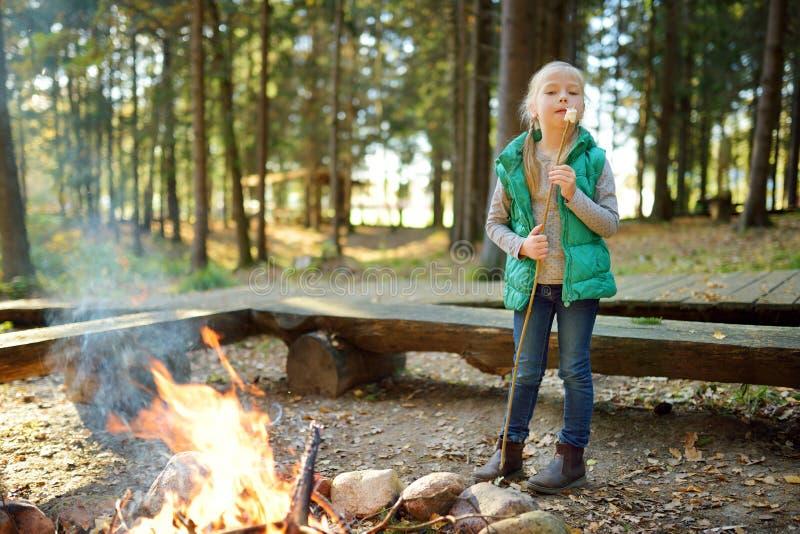 在棍子的逗人喜爱的女孩烤蛋白软糖在篝火 孩子获得乐趣在阵营火 野营与孩子在秋天森林里 免版税库存照片