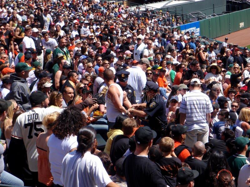在棒球期间,警察把爱好者扣上手铐在漂白剂 免版税库存照片