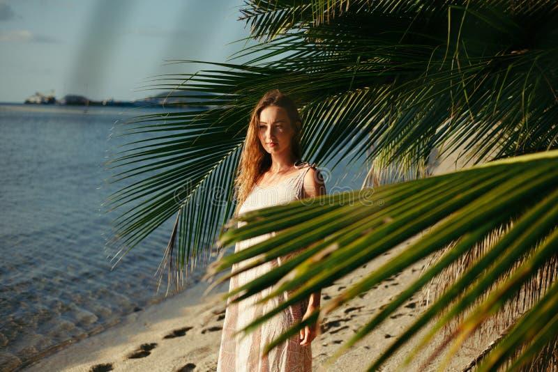 在棕榈树叶子之间的有吸引力的妇女身分 库存照片
