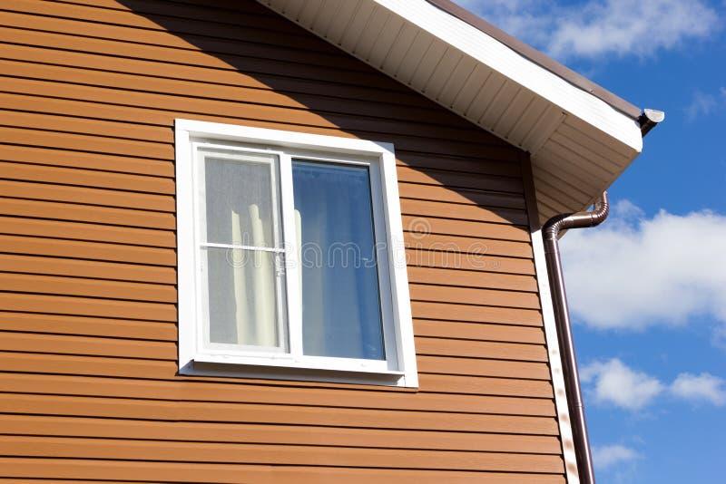 在棕色乙烯基房屋板壁墙壁的窗口  免版税库存图片