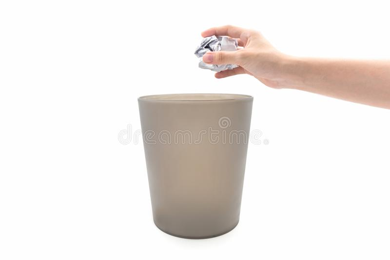 在棕色垃圾桶的特写镜头妇女手投掷的纸 免版税库存图片