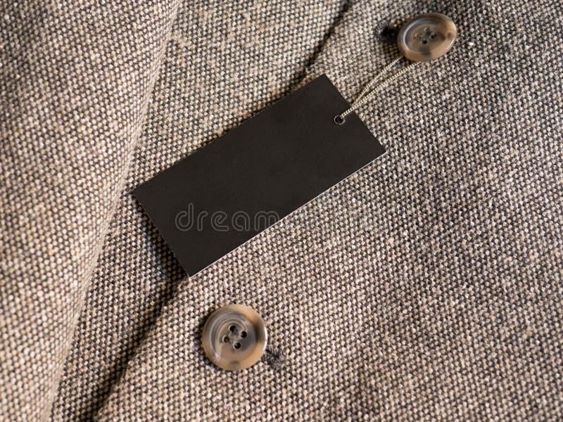 在棕色外套的空白的黑标签价牌大模型 免版税库存图片