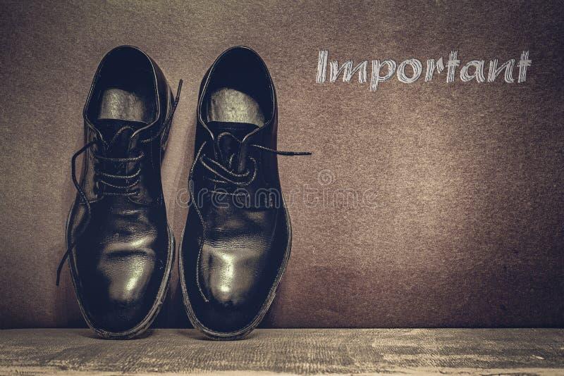 在棕色委员会的重要文本和在木地板上的工作鞋 免版税库存照片