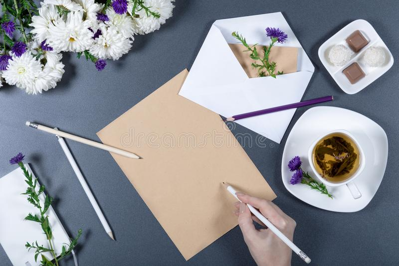 在棕色工艺纸一张的女性手文字  新chrys 免版税图库摄影