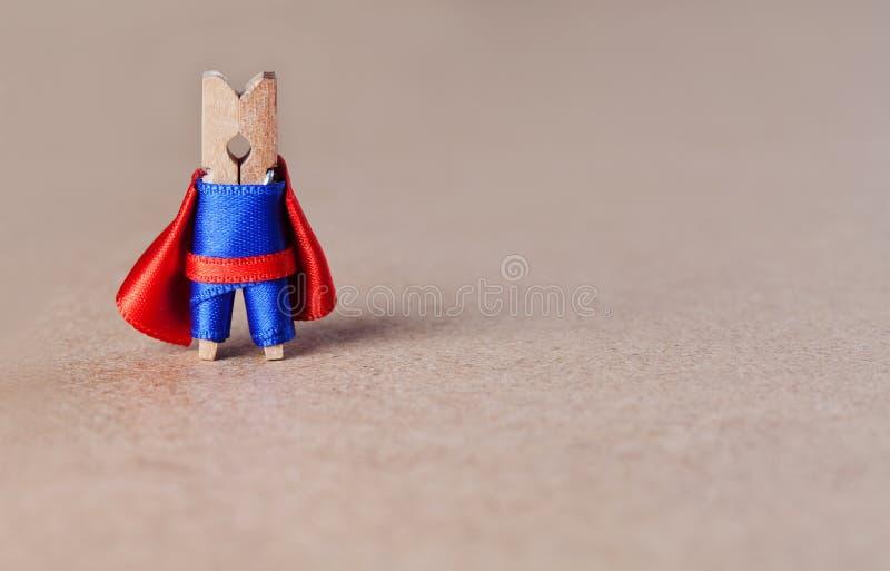 在棕色工艺纸背景的勇敢的晒衣夹超级英雄字符 蓝色衣服和红色海角玩具 领导概念 免版税库存图片
