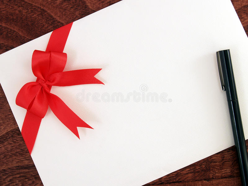 在棕色木地板上的贺卡和笔特写镜头白色信封与红色丝带弓的 库存照片