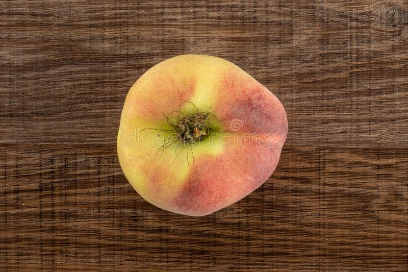 在棕色木头的新鲜的未加工的土星桃子 库存照片