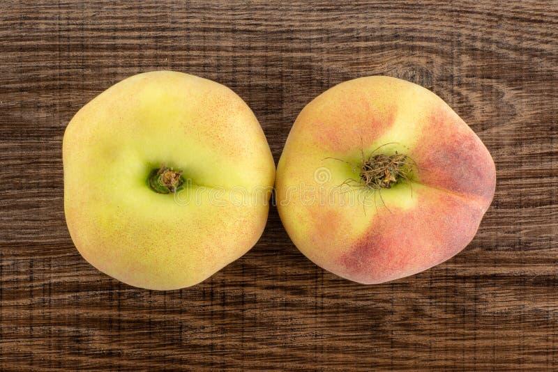 在棕色木头的新鲜的未加工的土星桃子 免版税库存图片