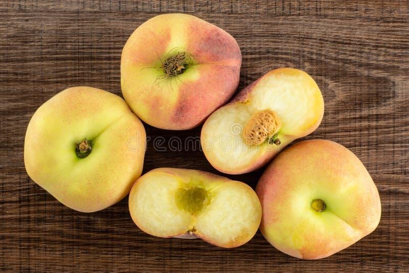 在棕色木头的新鲜的未加工的土星桃子 免版税图库摄影