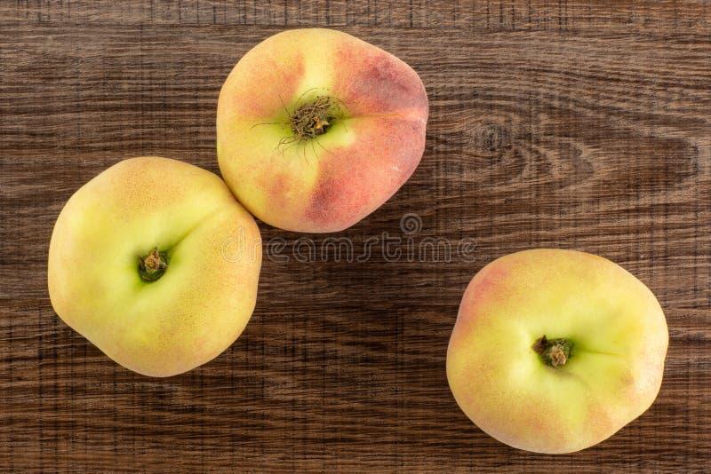 在棕色木头的新鲜的未加工的土星桃子 图库摄影