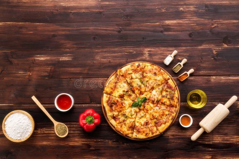 在棕色木桌上服务的新鲜的比萨顶视图,与成份和厨房设备 库存照片