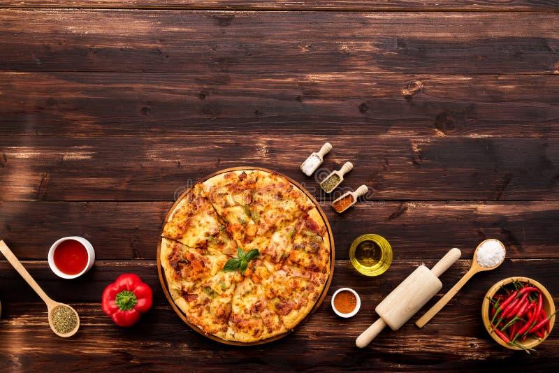 在棕色木桌上服务的新鲜的比萨顶视图,与成份和厨房设备 图库摄影