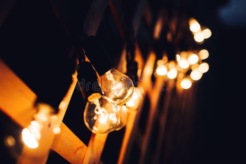 在棕色木桌上的发光的电灯泡独特概念 库存图片