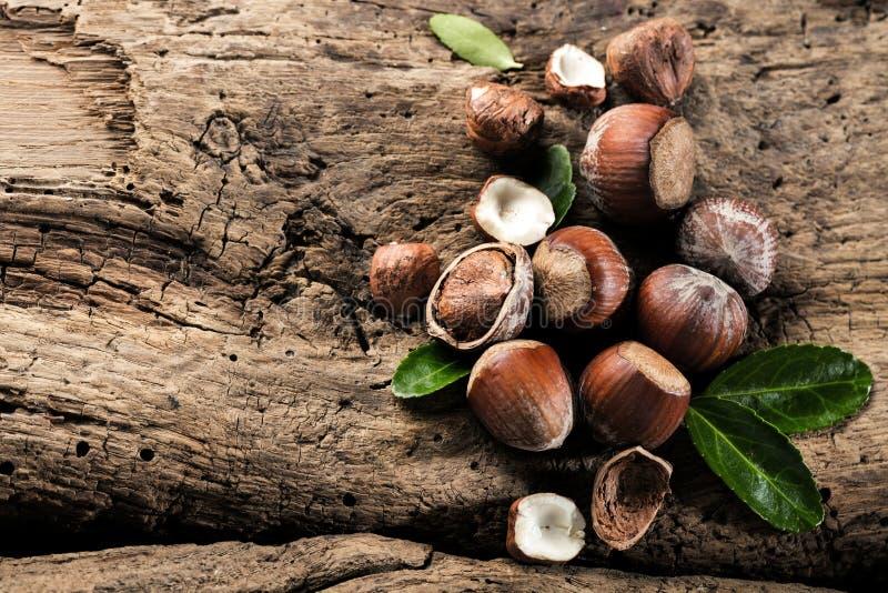 在棕色木背景关闭的榛子 免版税库存图片
