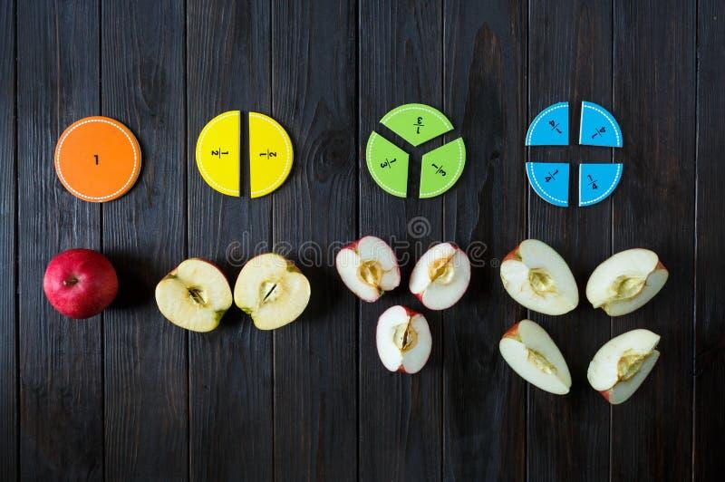 在棕色木背景或桌的五颜六色的算术分数 孩子的有趣的算术 教育,回到学校概念 免版税库存照片