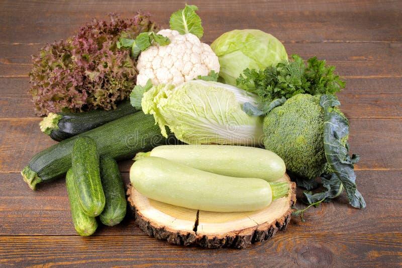 在棕色木背景的不同的新鲜,绿色菜 免版税库存照片