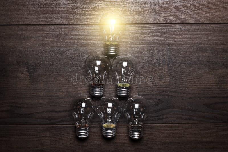 在木的发光的电灯泡领导概念 免版税图库摄影
