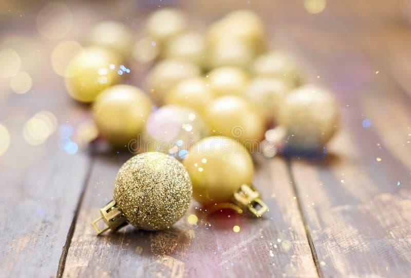 在棕色木背景的圣诞节金黄闪烁的球 图库摄影