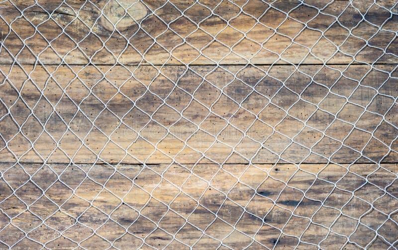 在棕色木背景的捕鱼网 免版税库存照片