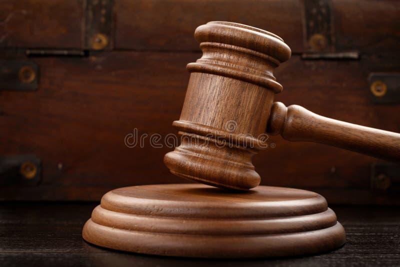 在棕色木背景的法官锤子 库存照片
