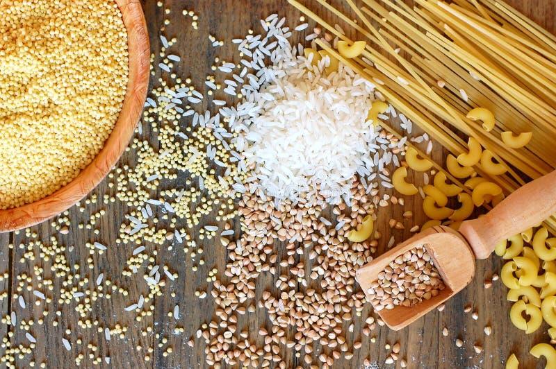 在棕色木背景的面筋免费谷物玉米、米、荞麦、奎奴亚藜、小米和面团和面粉 免版税库存照片