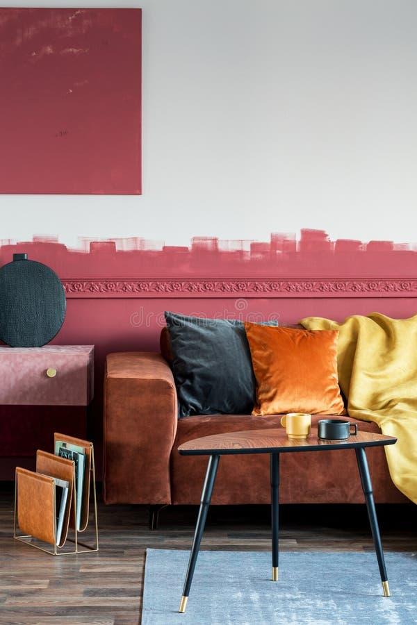 在棕色沙发的橙色枕头在与绒面革洗脸台和木咖啡桌的时兴的客厅内部 免版税库存照片