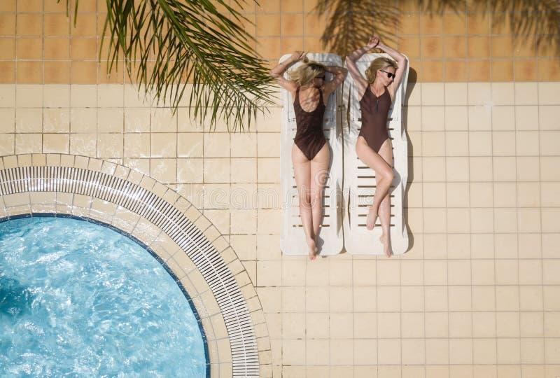 在棕色泳装的美丽的白肤金发的式样妇女孪生,在sunbed放置,享受夏天阳光,在游泳场旁边 免版税图库摄影