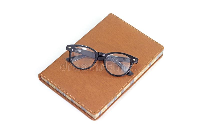 在棕色盖子的书有读书镜片的 库存照片