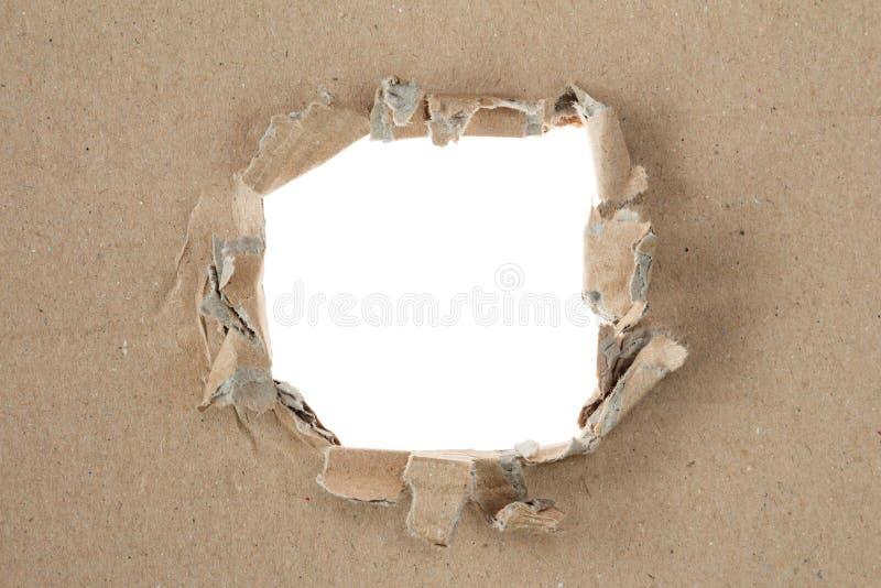 在棕色纸板的被剥去的孔 免版税库存图片