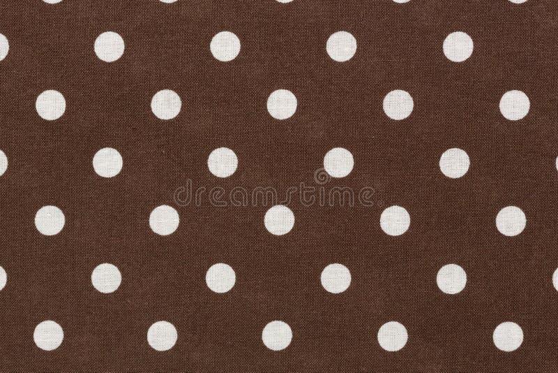 在棕色织品背景的白色圆点 库存照片