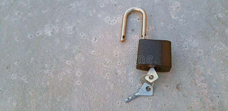 在棕色背景关闭的开锁的挂锁  免版税库存图片