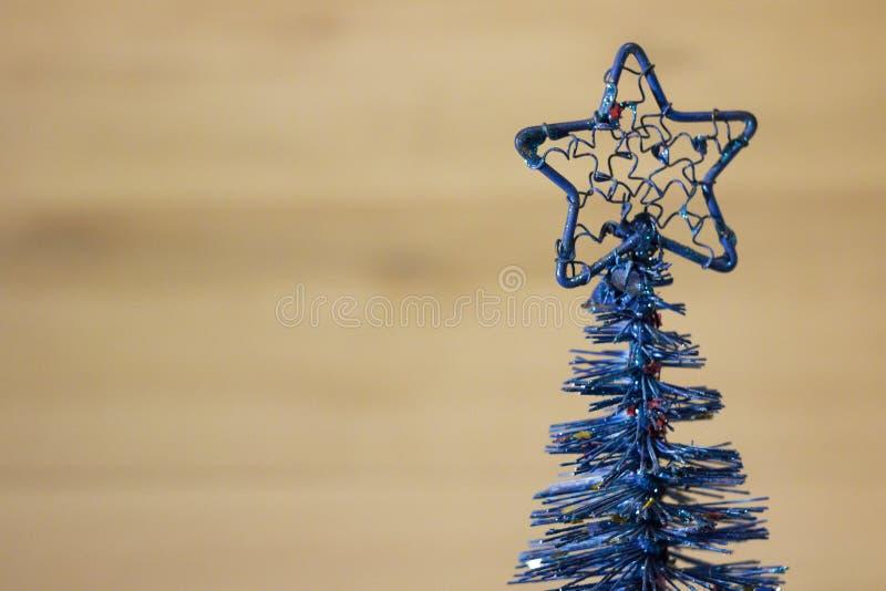 在棕色背景的圣诞节人为矮小的蓝色圣诞树 库存照片