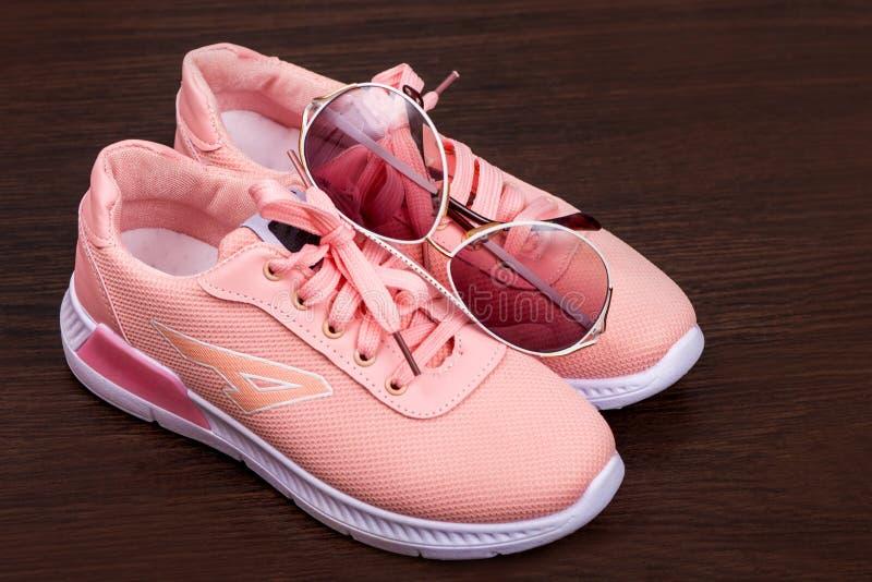 棕色背景的粉色运动鞋 白框中的点 运动鞋 时尚鞋 女式面料运动鞋 闪 免版税库存图片