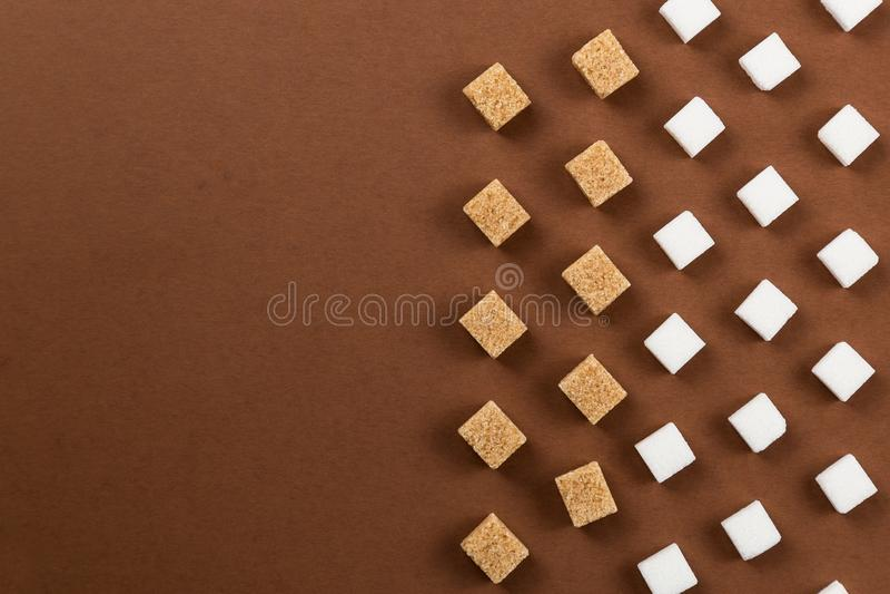 在棕色背景的布朗和白糖立方体 免版税图库摄影