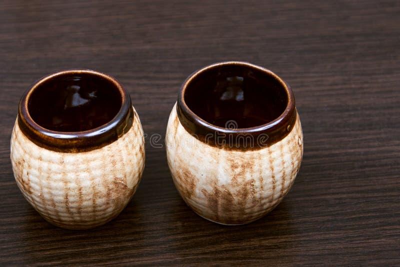 在棕色背景的老水罐 棕色瓷茶杯 陶瓷罐头 刺激小 布朗黏土盘 泥罐做了黏土 免版税库存照片